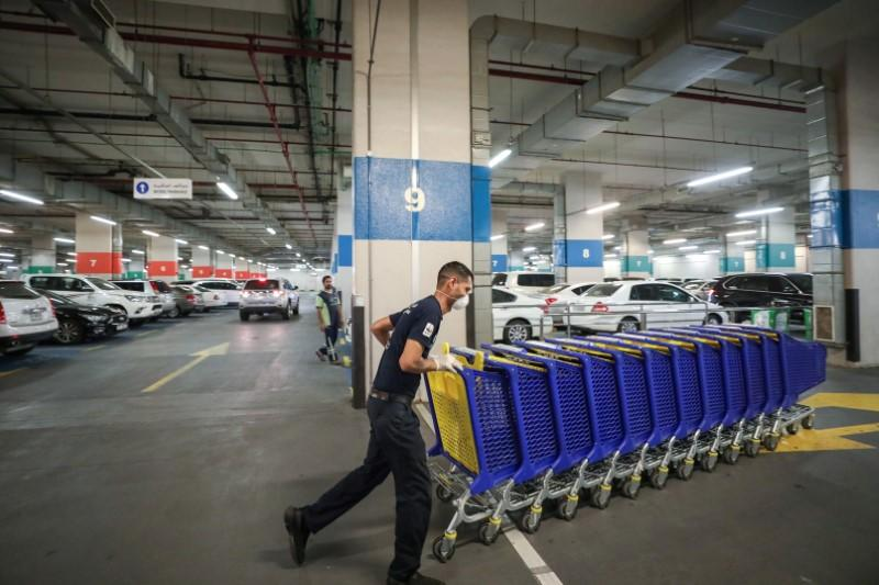 A worker wearing a face mask, amid fear of coronavirus disease (COVID-19) outbreak, pushes shopping carts at corporate Union shopping center in Dubai