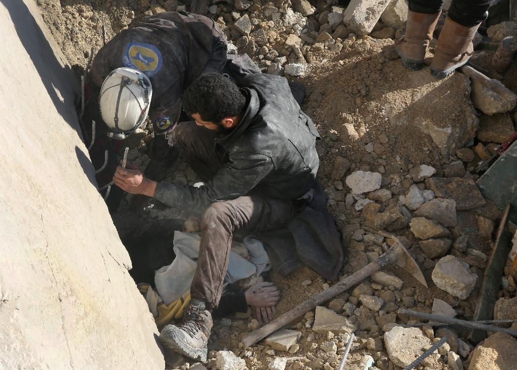 Syrian rescuers remove a victim from under the rubble following a reported air strike on the rebel-held neighbourhood of al-Kalasa in the northern Syrian city of Aleppo, on February 4, 2016 (AFP Photo/Thaer Mohammed)