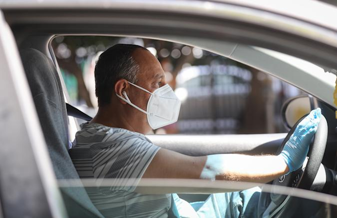 LOS ANGELES, CALIFORNIA - APRIL 16: A protestor wears a face mask and gloves as Uber and Lyft drivers with Rideshare Drivers United and the Transport Workers Union of America conduct a 'caravan protest' outside the California Labor Commissioner's office amidst the coronavirus pandemic on April 16, 2020 in Los Angeles, California. The drivers called for California to enforce the AB 5 law so that they may qualify for unemployment insurance as the spread of COVID-19 continues. Drivers also called for receiving back wages they say they are owed. (Photo by Mario Tama/Getty Images)
