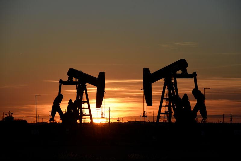 Pump jacks operate at sunset in an oil field in Midland