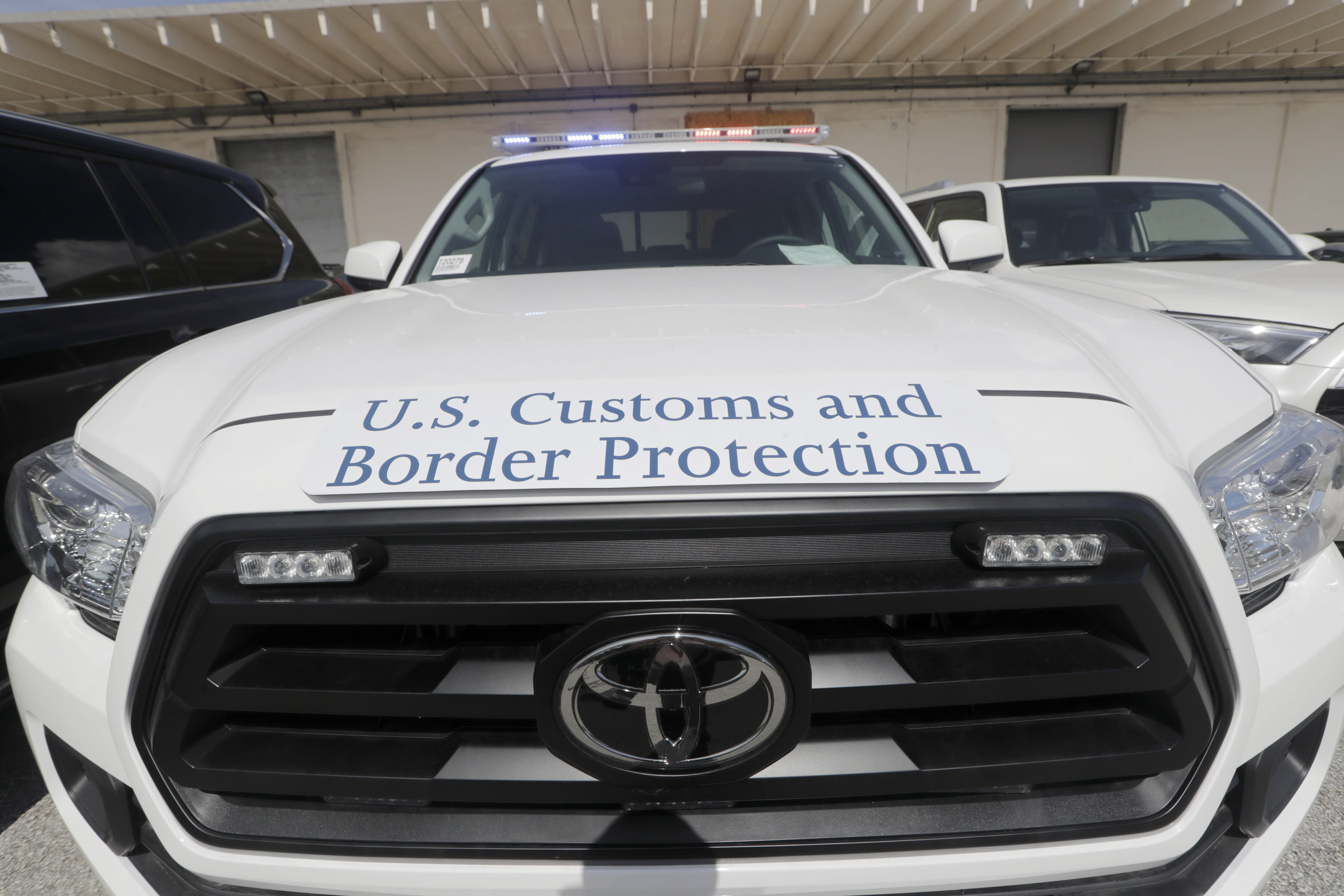 A Toyota Tacoma with flashing lights sits among vehicles worth an estimated $3.2 million, at Port Everglades after they were seized by Homeland Security Investigations, Wednesday, July 8, 2020, in Fort Lauderdale, Fla. The vehicles were to be smuggled to Venezuela in violation of U.S. export laws and sanctions against the socialist Venezuelan Government. (AP Photo/Lynne Sladky)