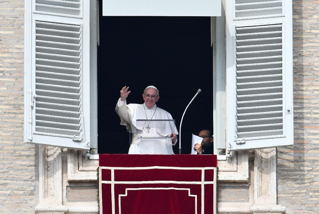 Pope Francis waves to pilgrims gathered in St. Peter's square during his Sunday Angelus prayer on February 12, 2017 at the Vatican