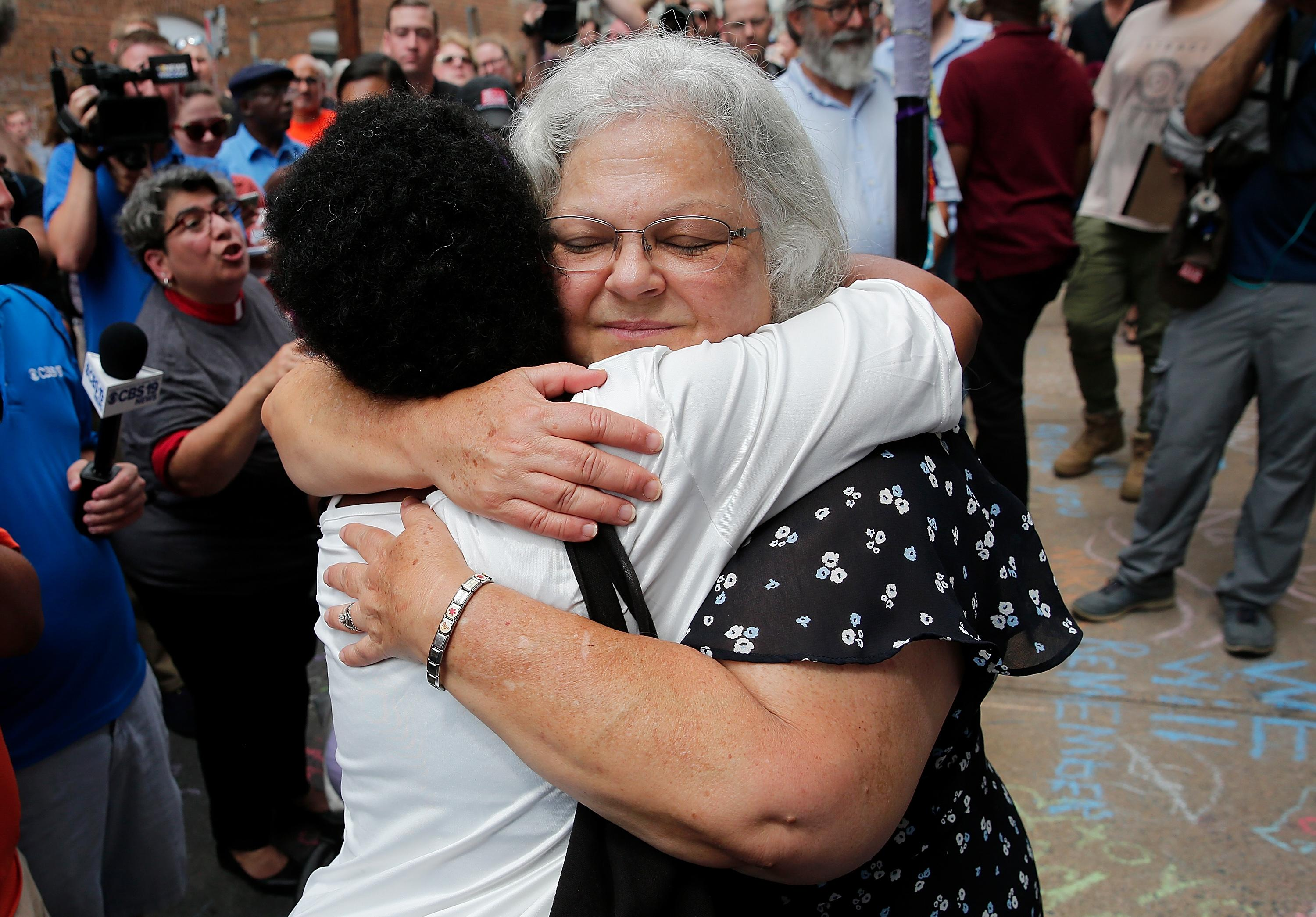"""<p>Susan Bro (R), mother of Heather Heyer, hugs a young woman near a makeshift memorial for her daughter Heather who was killed one year ago during a deadly clash, August 12, 2018 in Charlottesville, Virginia. Charlottesville has been declared in a state of emergency by Virginia Gov. Ralph Northam as the city braces for the one year anniversary of the deadly clash between white supremacist forces and counter protesters over the potential removal of Confederate statues of Robert E. Lee and Jackson. A """"Unite the Right"""" rally featuring some of the same groups is planned for today in Washington, DC. (Photo: Win McNamee/Getty Images) </p>"""