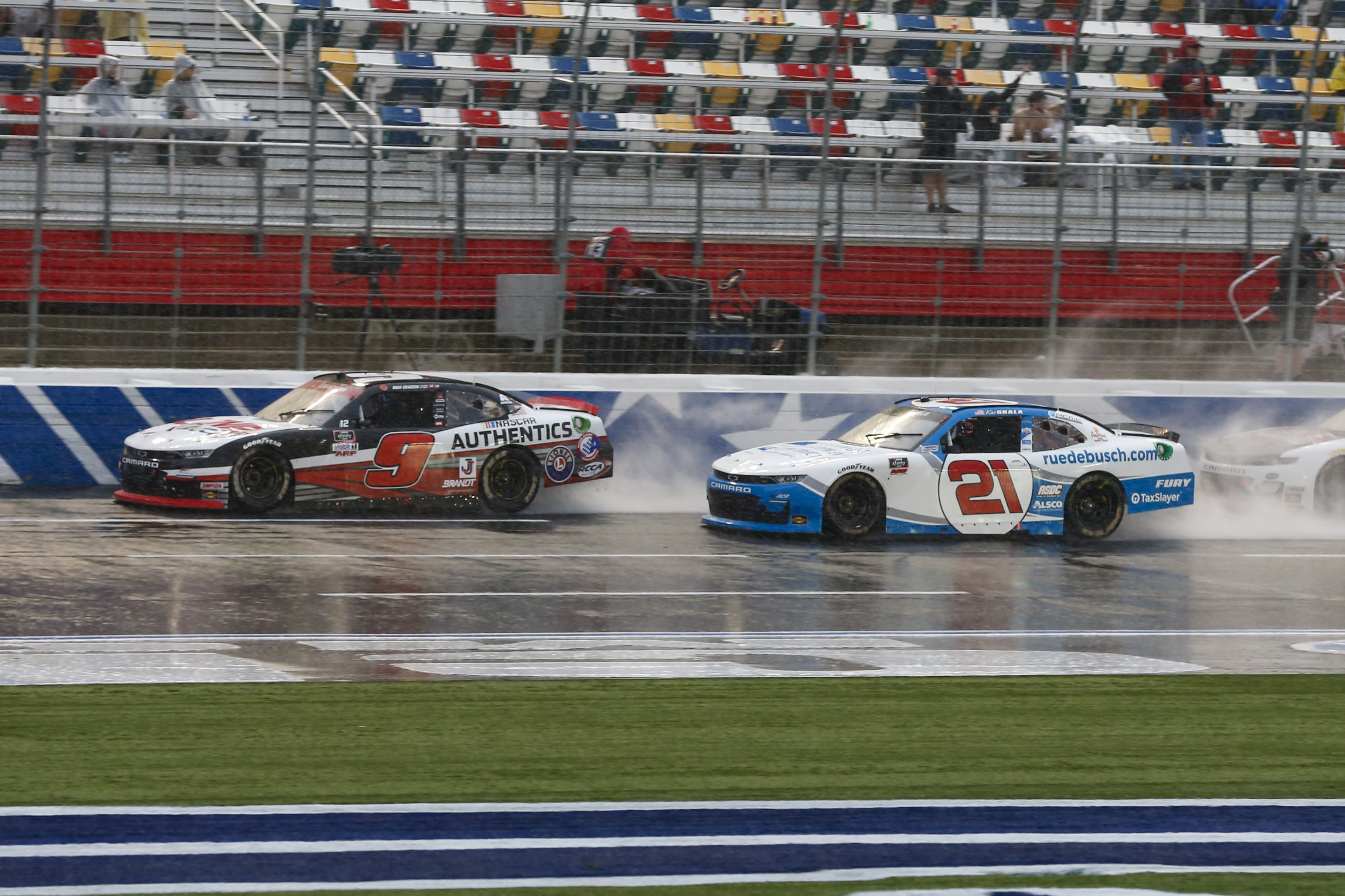Noah Gragson (9) and Kaz Grala (21) compete in the rain during a NASCAR Xfinity Series auto race at Charlotte Motor Speedway in Concord, N.C., Saturday, Oct. 10, 2020. (AP Photo/Nell Redmond)