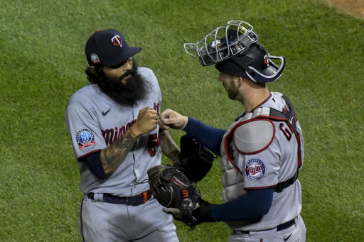 Minnesota Twins relief pitcher Sergio Romo, left, and catcher Mitch Garver, right, celebrate at end of a baseball game against the Chicago Cubs Sunday, Sept. 20, 2020, in Chicago. (AP Photo/Matt Marton)