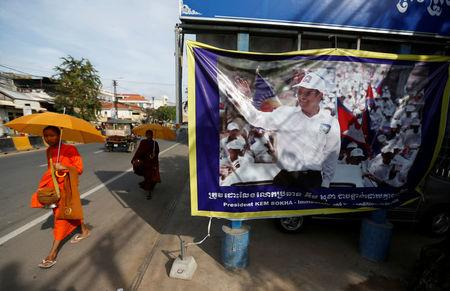 Buddhist monks walk past a banner of opposition leader and President of the Cambodia National Rescue Party (CNRP) Kem Sokha at the party's headquarters in Phnom Penh, Cambodia, November 17, 2017. REUTERS/Samrang Pring