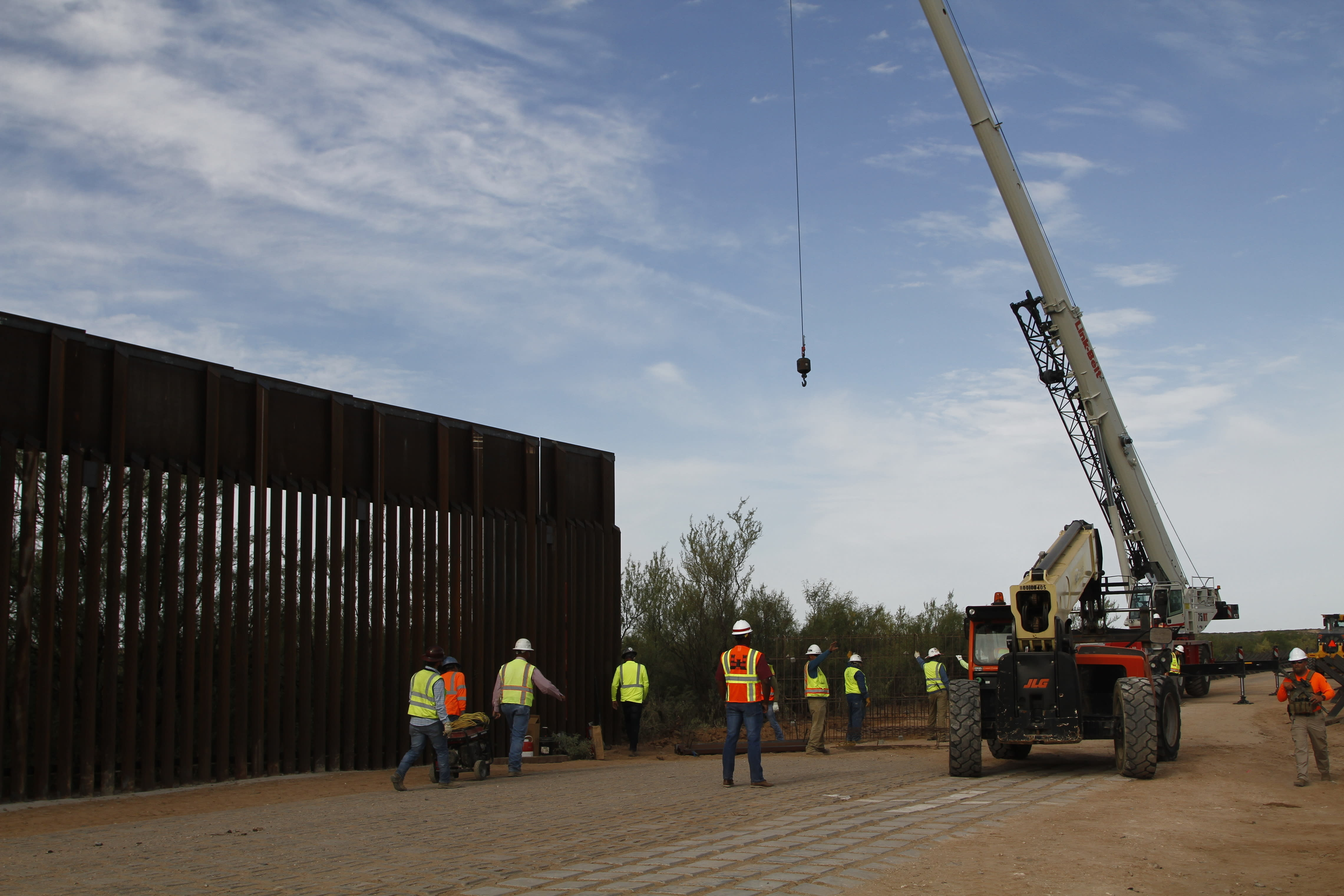 Workers break ground on new border wall construction about 20 miles west of Santa Teresa, New Mexico, Aug. 23, 2019. The wall visible on the left was built in 2018 with money allocated by Congress, while the new construction is funded by money reallocated from Department of Defense funding. (AP Photo/Cedar Attanasio)
