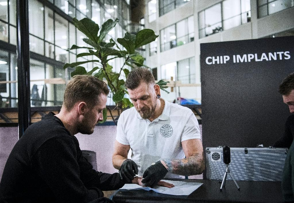 Jowan Osterlund (R), a piercings specialist and self-proclaimed champion of chip implantation, brushes off fears of data misuse and says if we carried all our personal data on us, we would have better control of their use (AFP Photo/Jonathan NACKSTRAND)