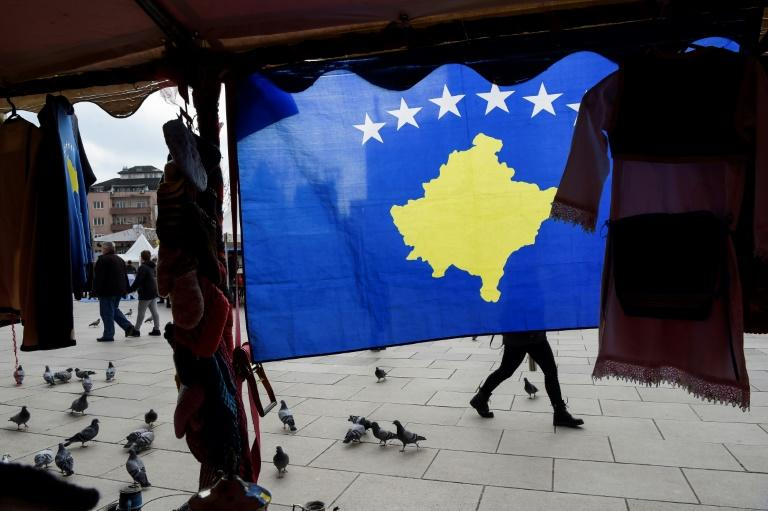 A pedestrian walks behind the Kosovo flag ahead of last year's 10th-anniversary celebrations in Pristina of Kosovo's declaration of independence