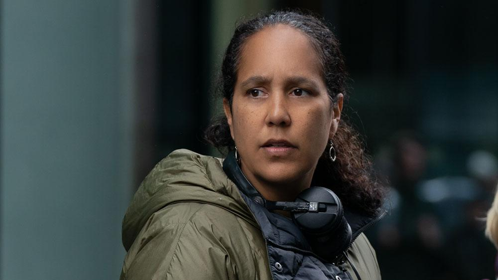 An image of director Gina Prince-Bythewood making The Old Guard. She is a Black woman aged 50, wearing her long curly hair pulled back in a low ponytail. She is wearing an olive green waterproof coat and a pair of over-ear headphones around her neck. She is focused on something off-camera.