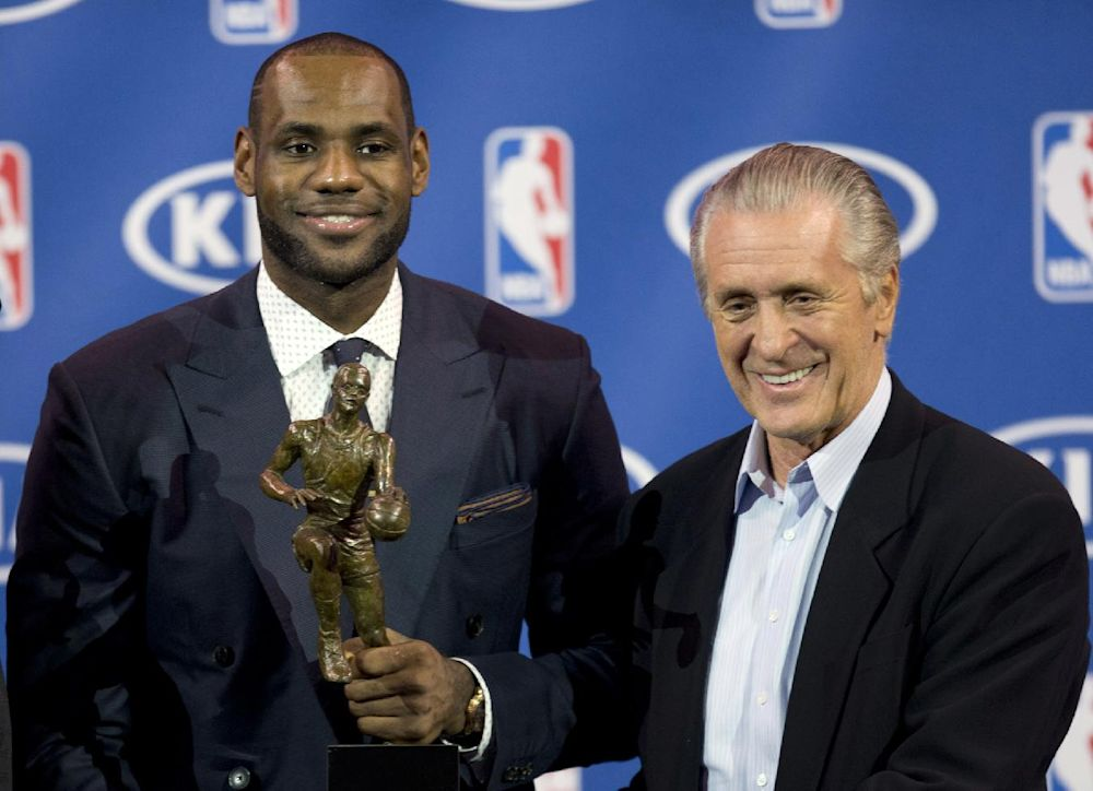 In this May 5, 2013 photo, Miami Heat NBA basketball player LeBron James, left, holds his NBA Most Valuable Player award as he poses with team president Pat Riley, in Miami. Before James makes his next decision, Riley will get a chance to convince him to stay in Miami. Two people familiar with the situation told The Associated Press late Sunday night, July 6, 2014, that James will meet with the Heat president this week before making a decision about where to play next season