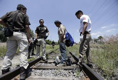Mexican immigration officers talk with a man whom they suspect to be an illegal immigrant during a search operation in Zapopan near Guadalajara, Mexico July 29, 2014. REUTERS/Alejandro Acosta/File Photo