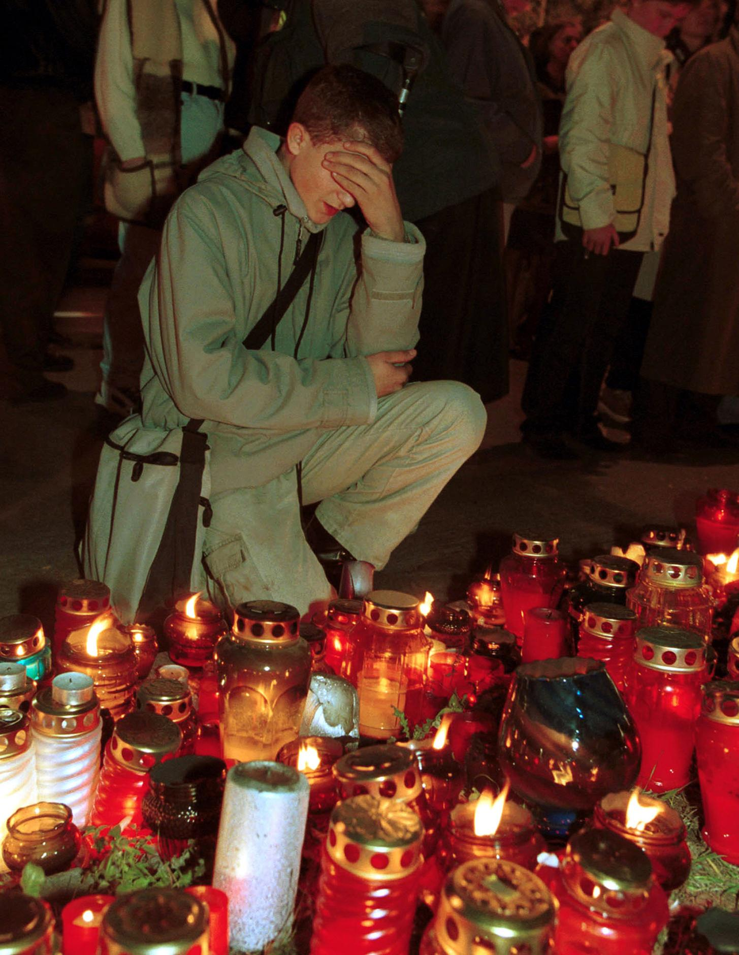 <p>An unidentified Warsaw resident prays in front of candles placed outside th U.S. embassy in Warsaw Wednesday Sept.12,2001. People kept coming to light candles and place flowers in front of the embassy in memory of the victims of the terrorist attacks in New York and Washington. (AP Photo/Alik Keplicz) </p>