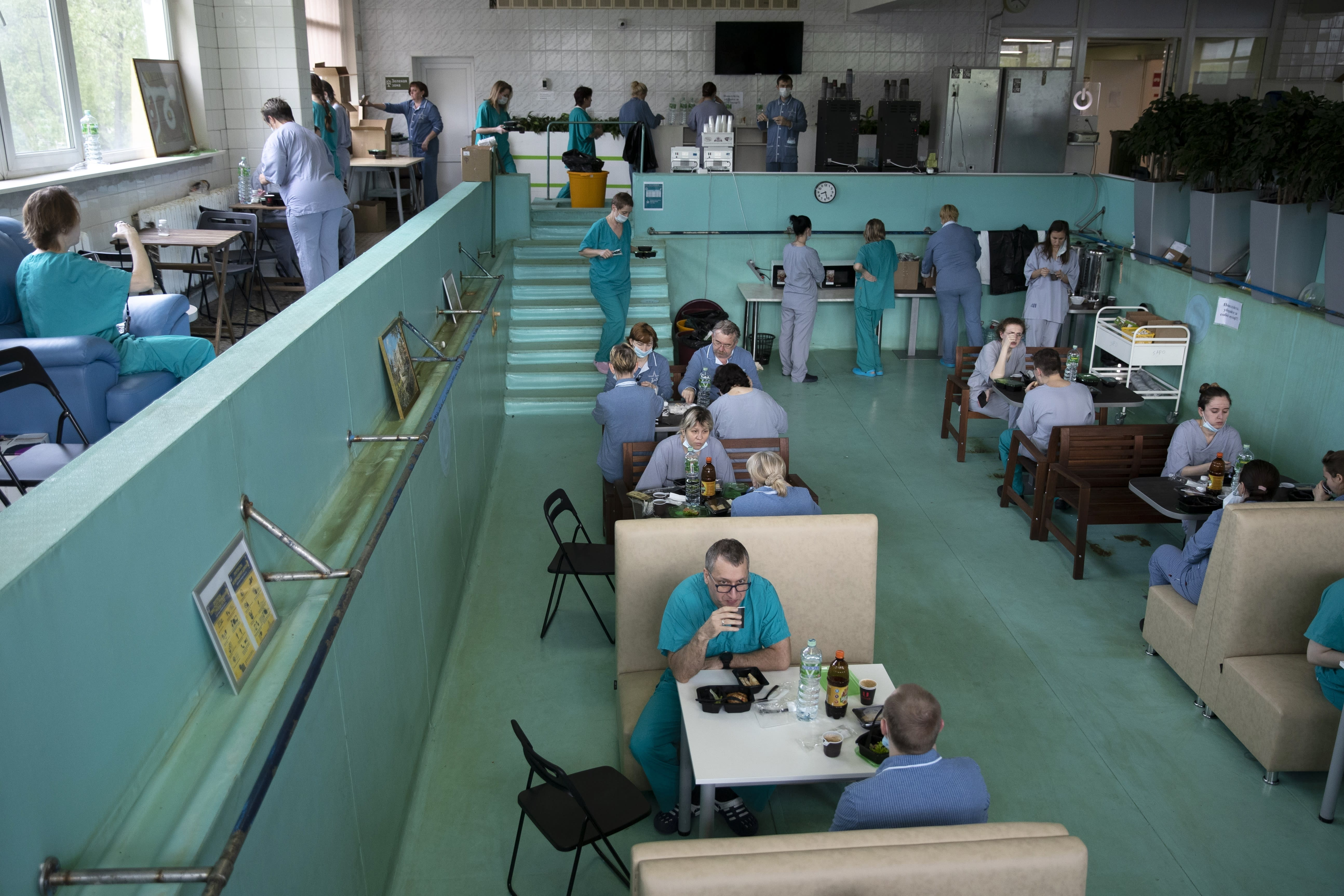 In this photo taken on Friday, May 15, 2020, Dr. Osman Osmanov, center, has breakfast before his shift at an intensive care unit of the Filatov City Clinical Hospital in Moscow, Russia. Moscow accounts for about half of all of Russia's coronavirus cases, a deluge that strains the city's hospitals and has forced Osmanov to to work every day for the past two months, sometimes for 24 hours in a row. (AP Photo/Pavel Golovkin)