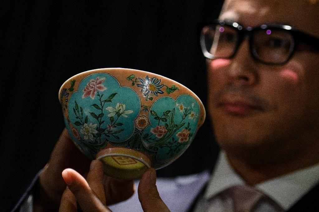 Nicolas Chow, deputy chairman of Sotheby's Asia, holds an extremely rare Qing Dynasty bowl -- one of only three known to exist -- during a media preview. It sold for US$30.4 million
