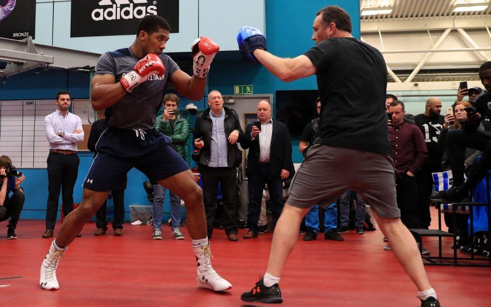 Anthony Joshua spars with trainerRobert McCracken (R) - PA