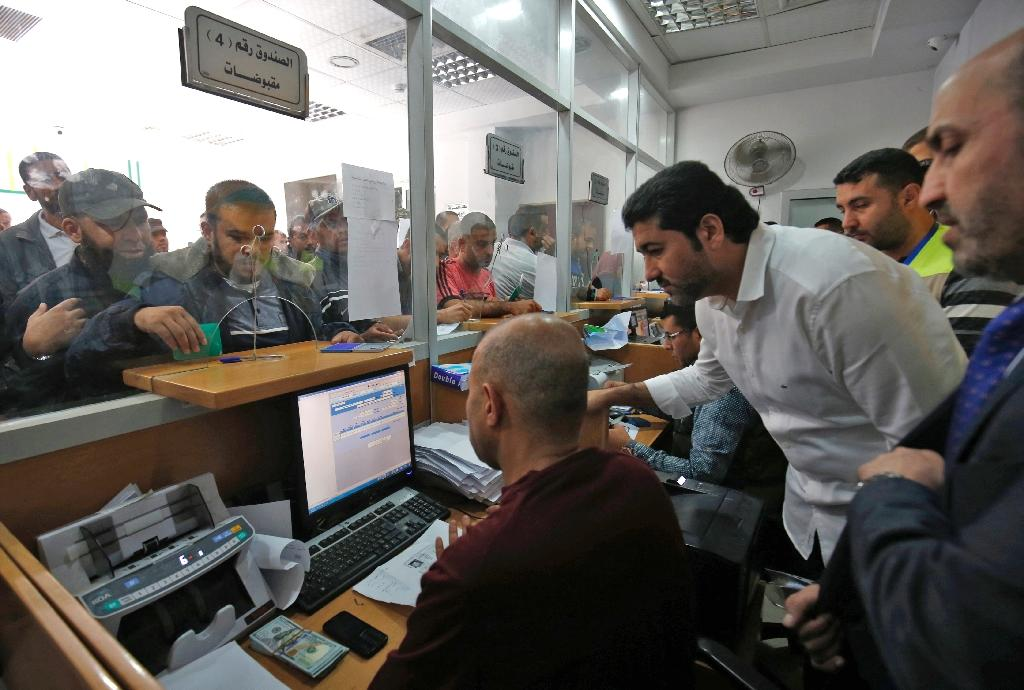 Palestinians line up to receive their delayed salaries in the cash-strapped Gaza Strip on November 9, 2018 after Israel authorised Qatar to transfer funds into the territory (AFP Photo/Said KHATIB)