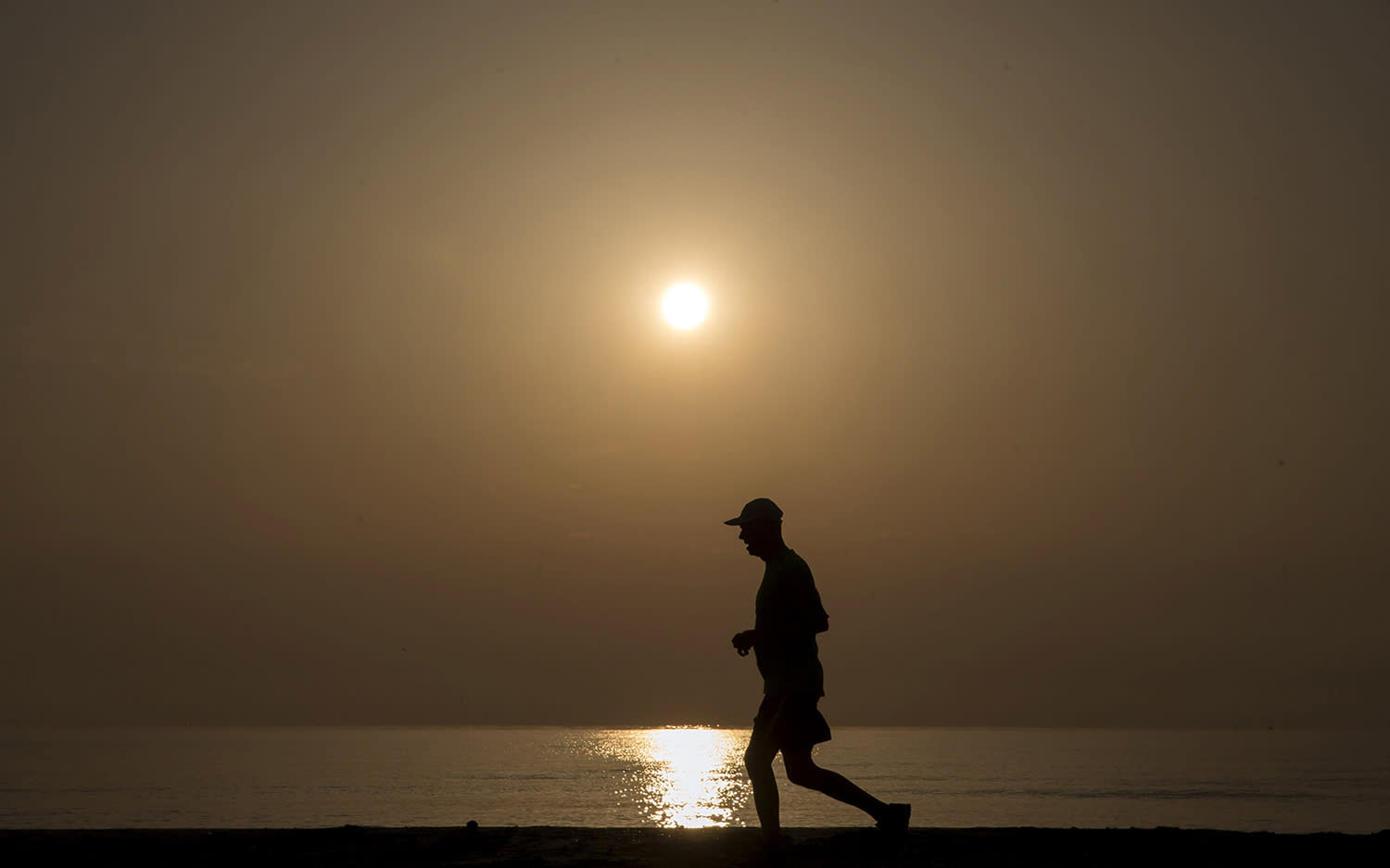 <p>A man jogs during dawn at the beach of la Malvarrosa, Valencia, eastern Spain, April 14, 2017. (Photo: Kai Foersterling/EPA) </p>
