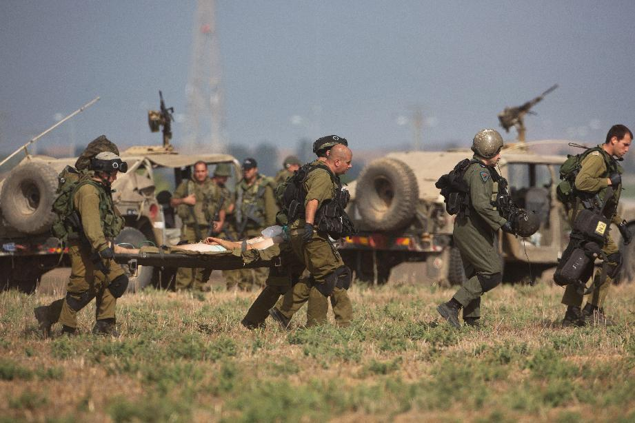 An injured soldier is evacuated from near the Israeli border with Gaza Strip, on July 21, 2014