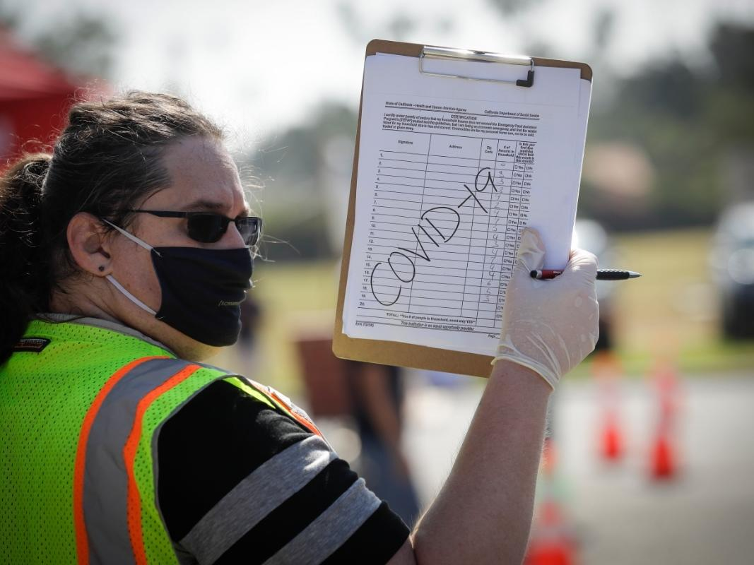 A volunteers directs traffic at a food distribution center Wednesday, July 22, 2020, in the Mission Hills area of Los Angeles.