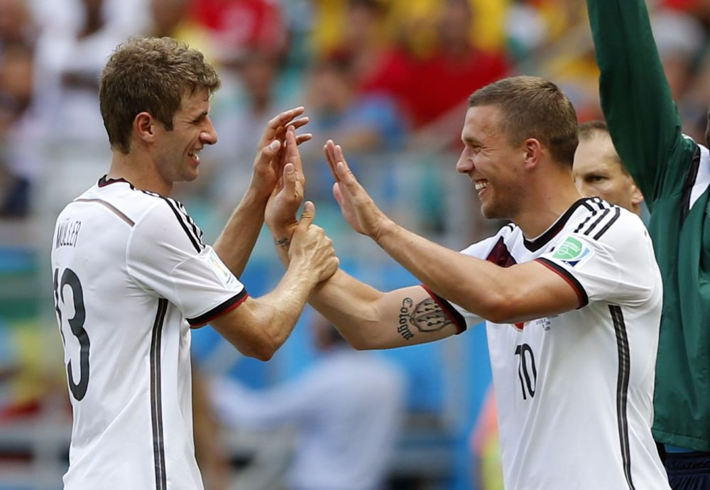 Germany's Thomas Mueller, left, is greeted by Lukas Podolski after being substituted after scoring a hat-trick during the group G World Cup soccer match between Germany and Portugal at the Arena Fonte Nova in Salvador, Brazil, Monday, June 16, 2014