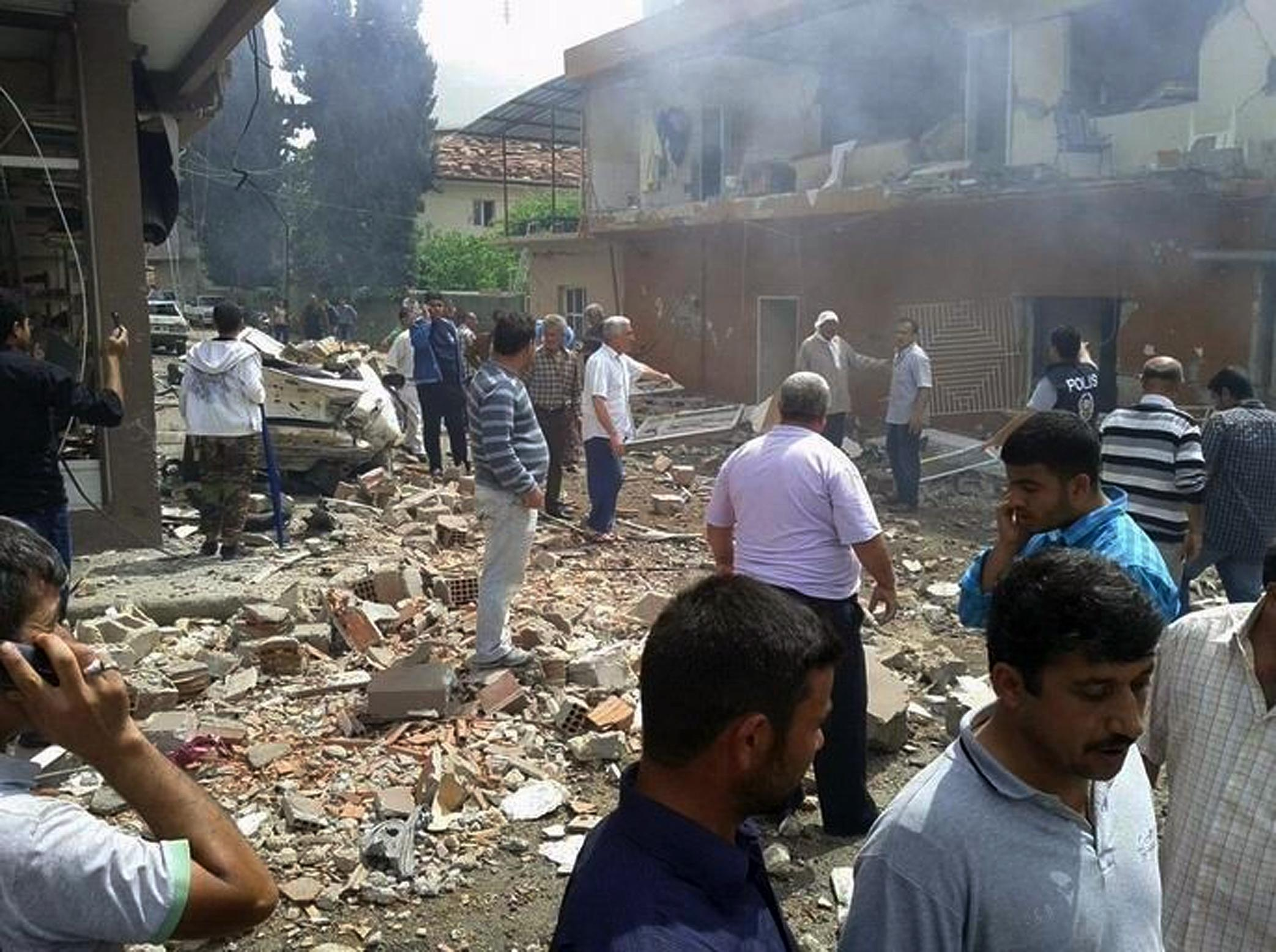 People gather at the site of a blast which killed and injured a number of people in Reyhanli, near Turkey's border with Syria, Saturday, May 11, 2013. Two car bombs exploded in a Turkish town near the border with Syria on Saturday, killing at least four people and injuring 22 others, officials and media reports said. (AP Photo/IHA) TURKEY OUT