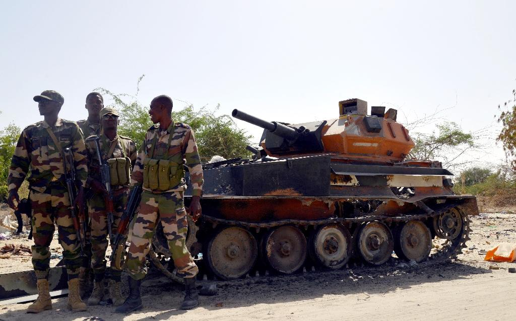 File picture shows Niger soldiers next to a burnt out tank belonging to the Boko Haram militants, in Malam Fatori, in northern Nigeria, near the border with Niger