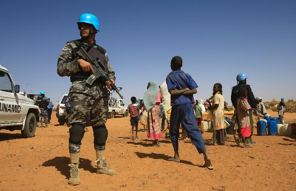 Sudanese people walk past a member of the UN-African Union mission in Darfur (UNAMID) at the Zamzam camp for Internally Displaced People (IDP), North Darfur, on April 9, 2015 (AFP Photo/Ashraf Shazly)