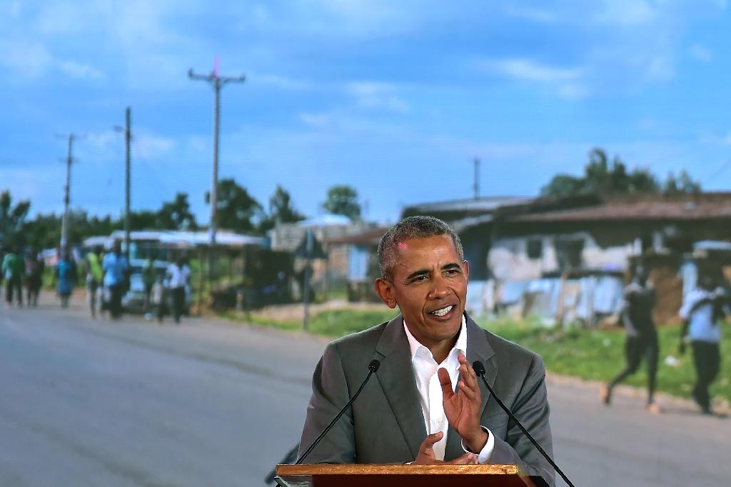 The former US president gave a speech in front of a projected backdrop showing a view of his father's home village (AFP Photo/TONY KARUMBA)
