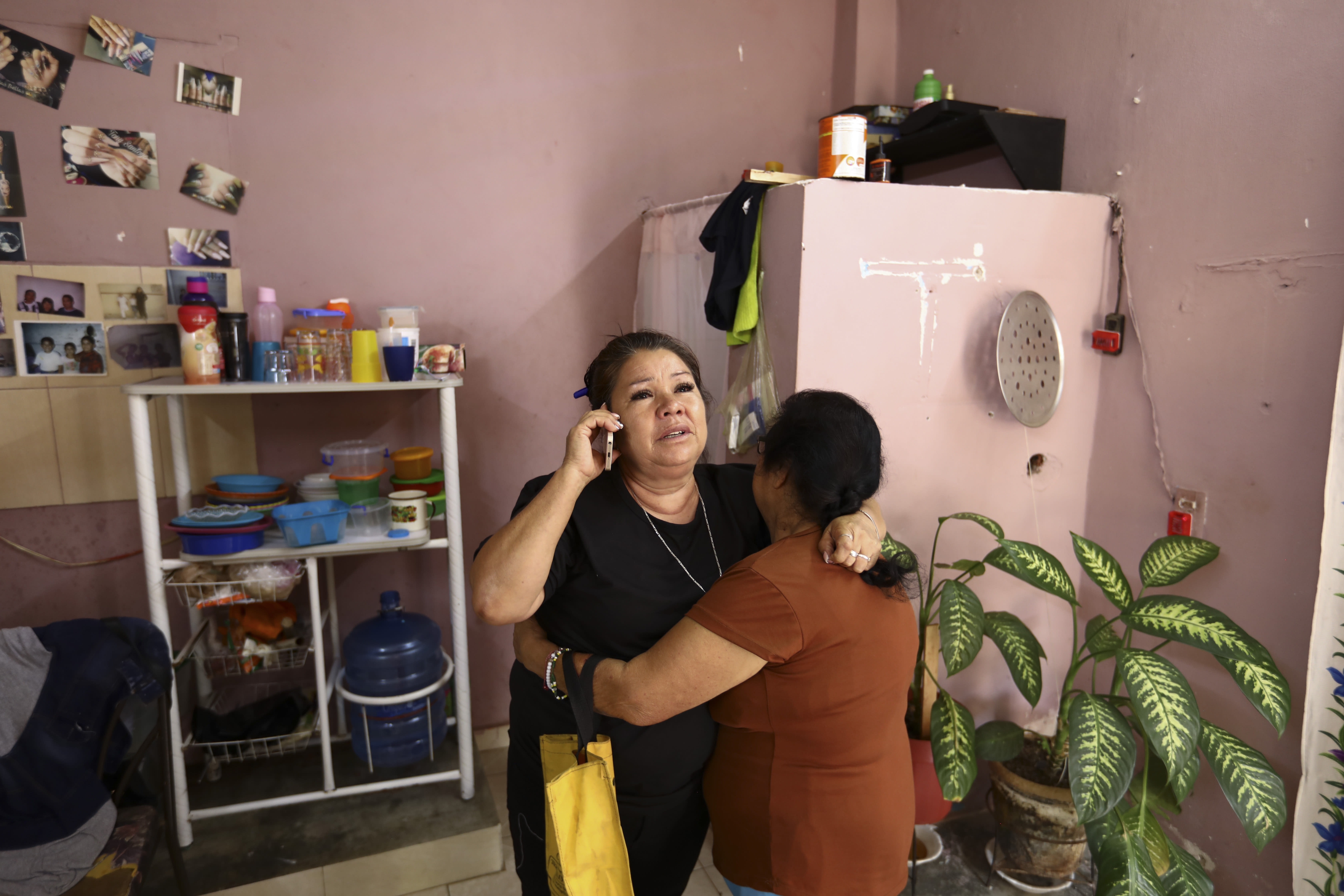 Rosa Alba Santoyo speaks on the phone and is embraced by a woman giving her condolences the day after she lost three of her adult children in an attack on the drug rehabilitation center where they were being treated, at her home in Irapuato, Mexico, Thursday, July 2, 2020. Gunmen burst into the drug rehabilitation center and opened fire Wednesday, killing 24 people and wounding seven, authorities said. After the loss of her three children, only two of Santoyo's seven children remain living. (AP Photo/Eduardo Verdugo)