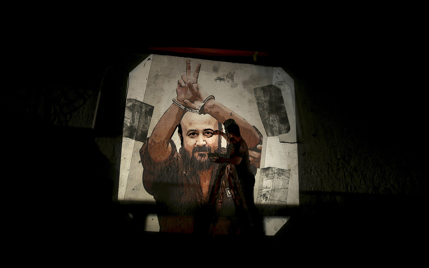 <p>A Palestinian paints an image depicting Palestinian leader and prominent prisoner Marwan Barghouti on a wall on the streets of Gaza City, May 25, 2017. (Photo: Mohammed Saber/EPA) </p>