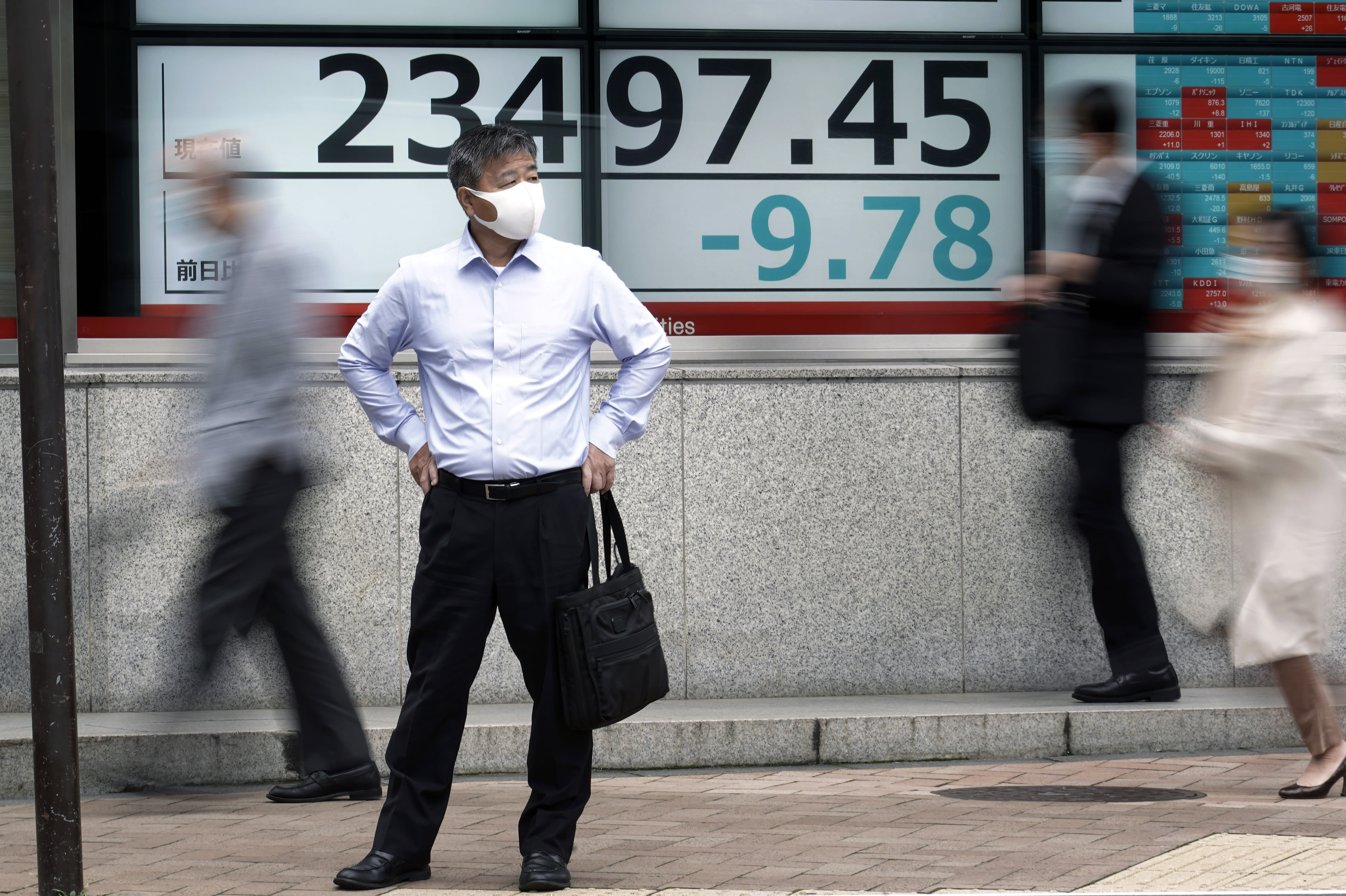 A man stands near an electronic stock board showing Japan's Nikkei 225 index at a securities firm in Tokyo Friday, Oct. 16, 2020. Asian shares were mixed on Friday as investors weighed concerns about the U.S. presidential election and an economic stimulus package, on top of fears of flaring outbreaks of coronavirus. (AP Photo/Eugene Hoshiko)