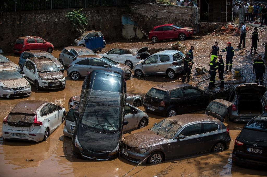 Emergency workers survey damage to vehicles in northern Athens on July 26, 2018, after a flash flood struck the Greek capital (AFP Photo/ANGELOS TZORTZINIS)