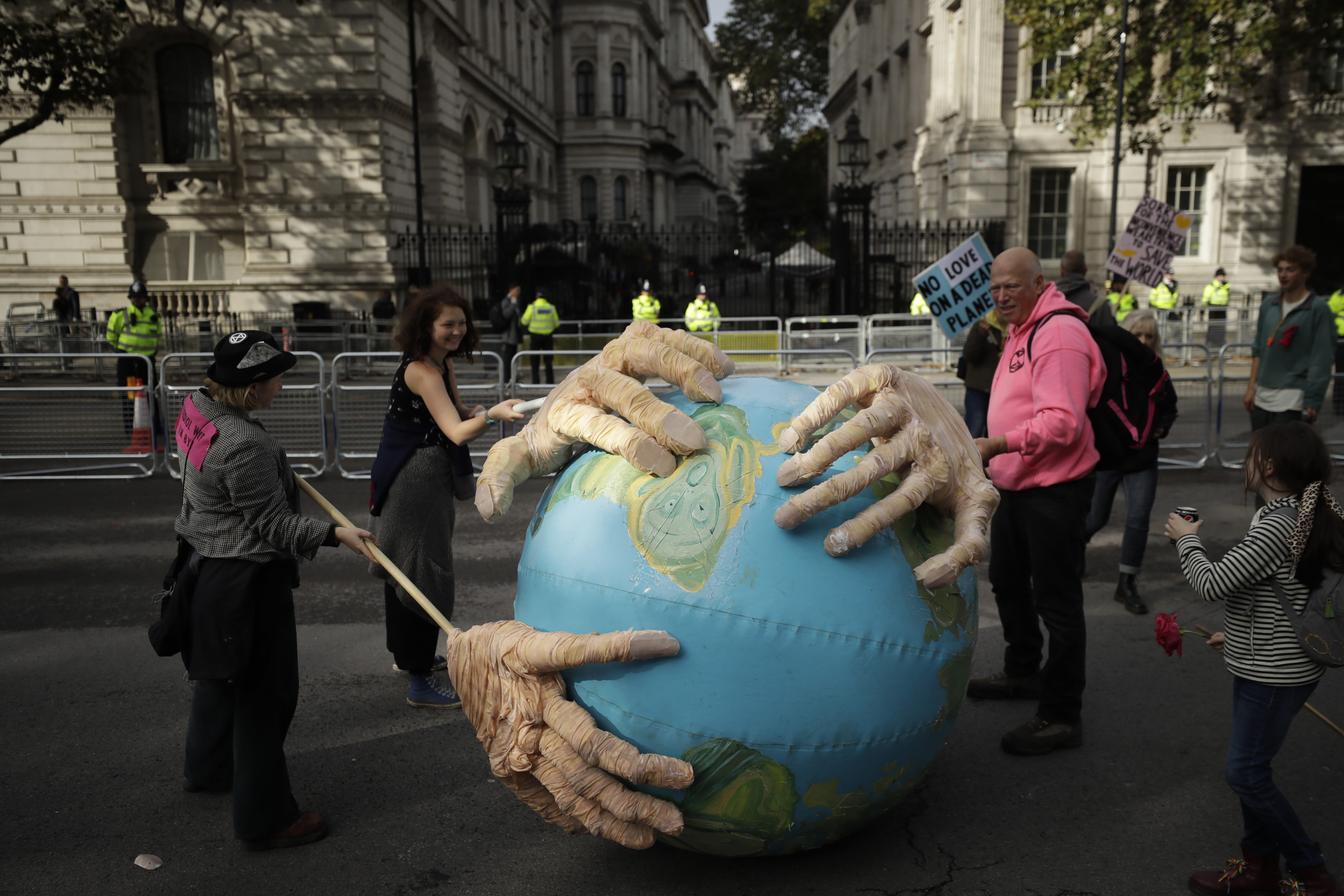 Extinction Rebellion climate change protesters demonstrate backdropped by the front gates of Downing Street in London, Tuesday, Oct. 8, 2019. Hundreds of climate change activists camped out in central London on Tuesday during a second day of world protests by the Extinction Rebellion movement to demand more urgent actions to counter global warming. (AP Photo/Matt Dunham)