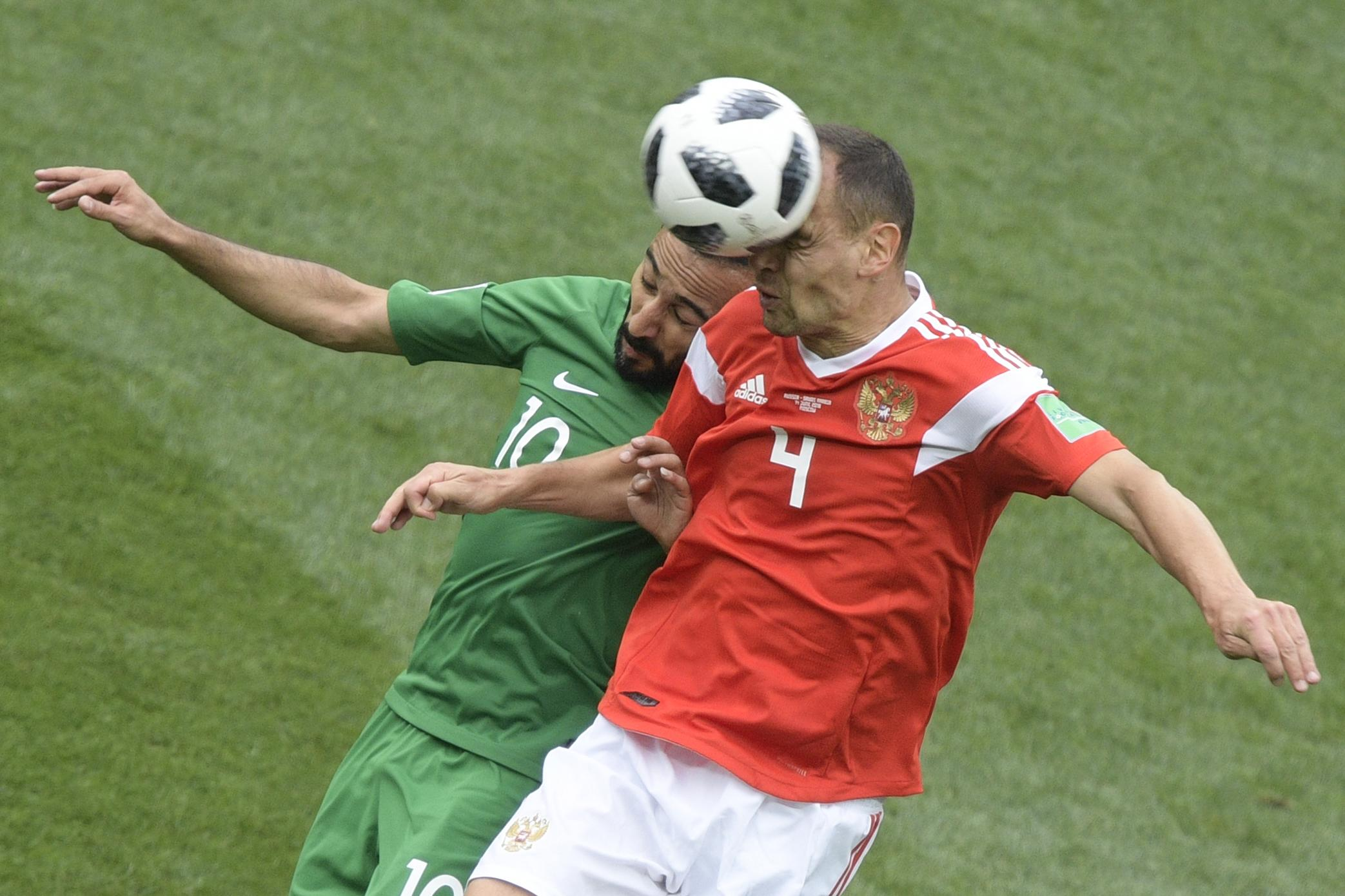 <p>Saudi Arabia's forward Mohammed Al-Sahlawi (L) and Russia's defender Sergey Ignashevich compete for the ball during the Russia 2018 World Cup Group A football match between Russia and Saudi Arabia at the Luzhniki Stadium in Moscow on June 14, 2018. (Photo by Juan Mabromata / AFP) / RESTRICTED TO EDITORIAL USE – NO MOBILE PUSH ALERTS/DOWNLOADS (Getty Images) </p>