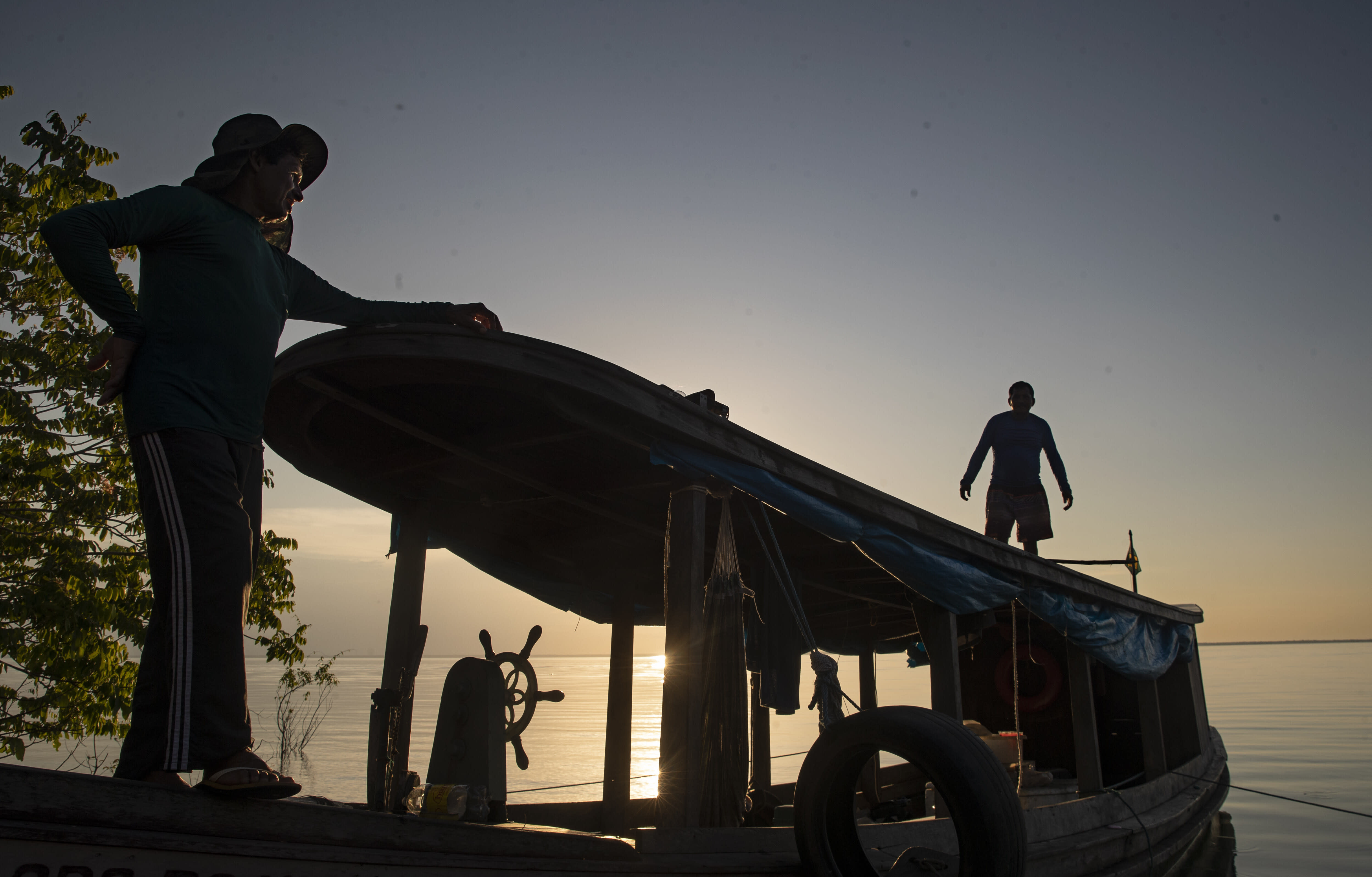 Fishermen walk on their boat as they fish in the Tapajos river in Alter do Chao, district of Santarem, Para state, Brazil, Thursday, Aug. 27, 2020. Last year a massive fire, whose origins are still under investigation, destroyed an area equivalent to 1,600 soccer fields in Alter do Chão. (AP Photo/Andre Penner)