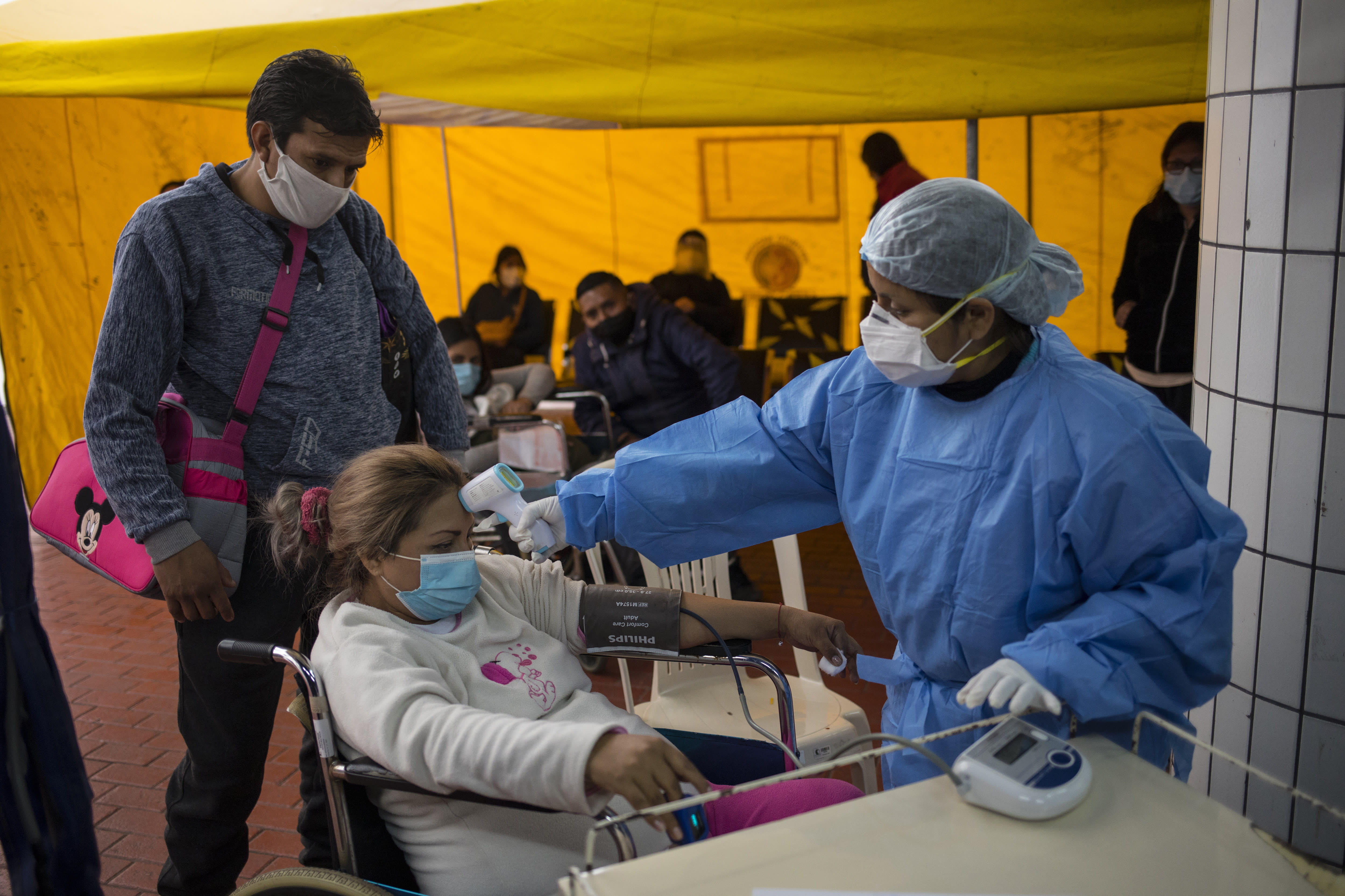 A healthcare worker measures the body temperature of Luisita Hermosillo, 32, as part of an initial check to identify if she is infected with the new coronavirus, at an entry pointy set up to receive pregnant women at the National Perinatal and Maternal Institute in Lima, Peru, Thursday, July 9, 2020. Because the Institute has barred partners or other relatives from attending births, women are giving birth alone. (AP Photo/Rodrigo Abd)