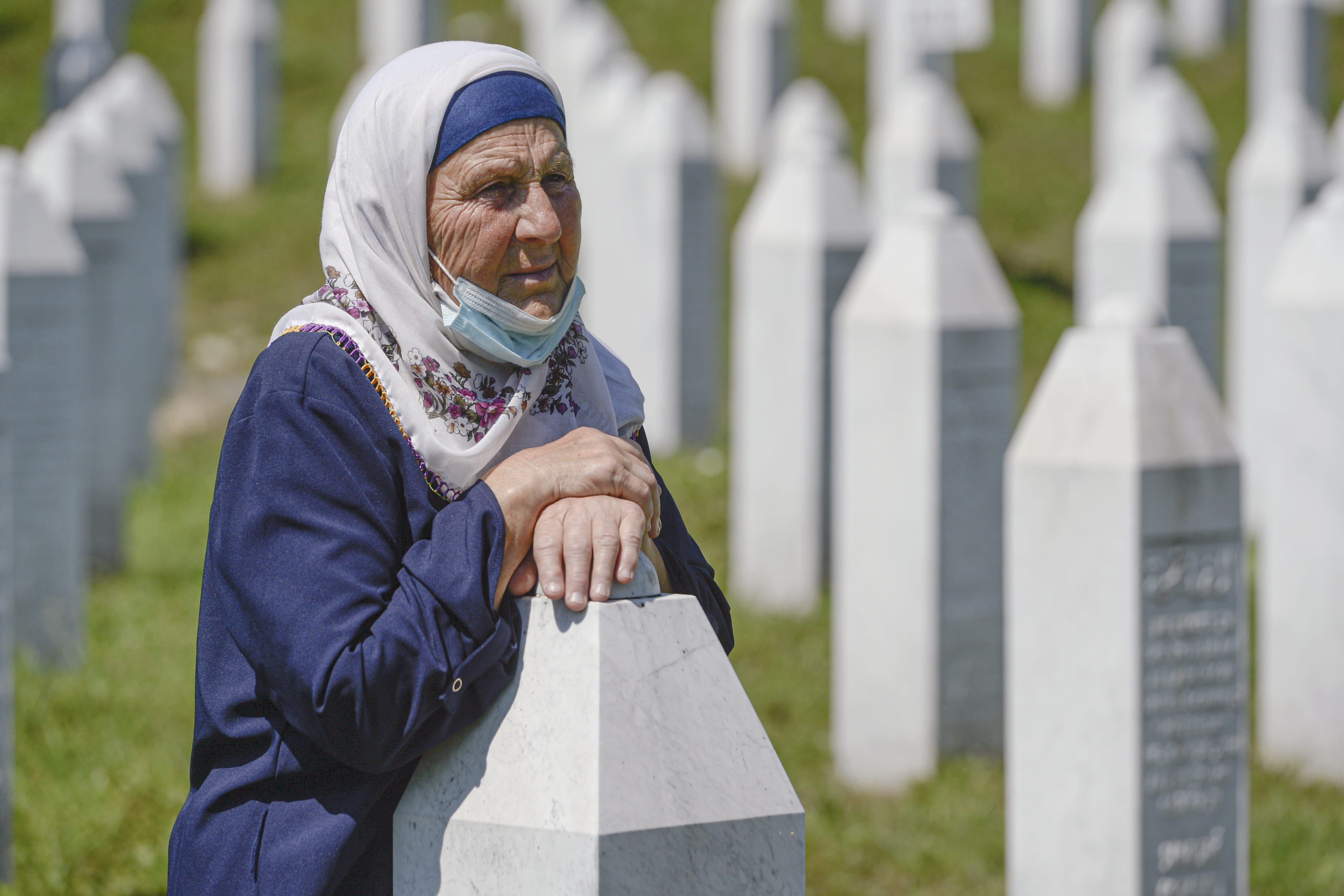 A woman leans on a grave stone in Potocari, near Srebrenica, Bosnia, Saturday, July 11, 2020. Mourners converged on the eastern Bosnian town of Srebrenica for the 25th anniversary of the country's worst carnage during the 1992-95 war and the only crime in Europe since World War II that has been declared a genocide. (AP Photo/Kemal Softic)