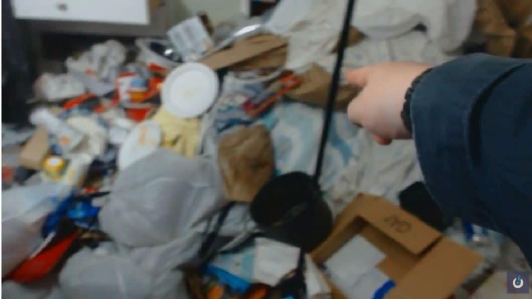 直播主指著自己堆滿垃圾的房間。(圖/翻攝自YouTube)