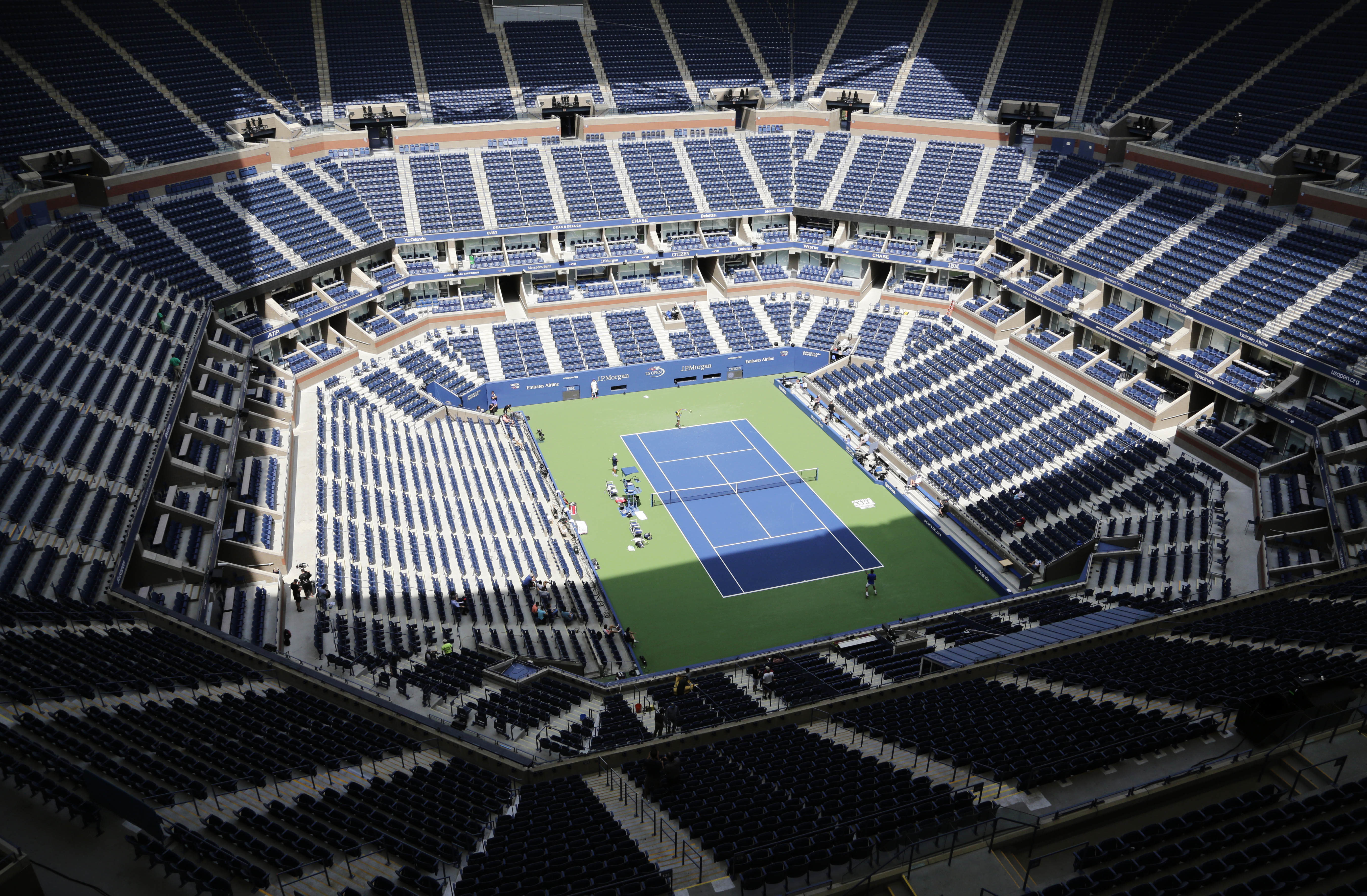 In this file photo from Aug. 27, 2017, players practice at the empty Arthur Ashe Stadium at the U.S. Open tennis tournament in New York. New York City's comptroller says the organizers of the U.S. Open tennis tournament owe the city $311,000 in back rent for use of the tournament site in Queens. (AP Photo/Peter Morgan)