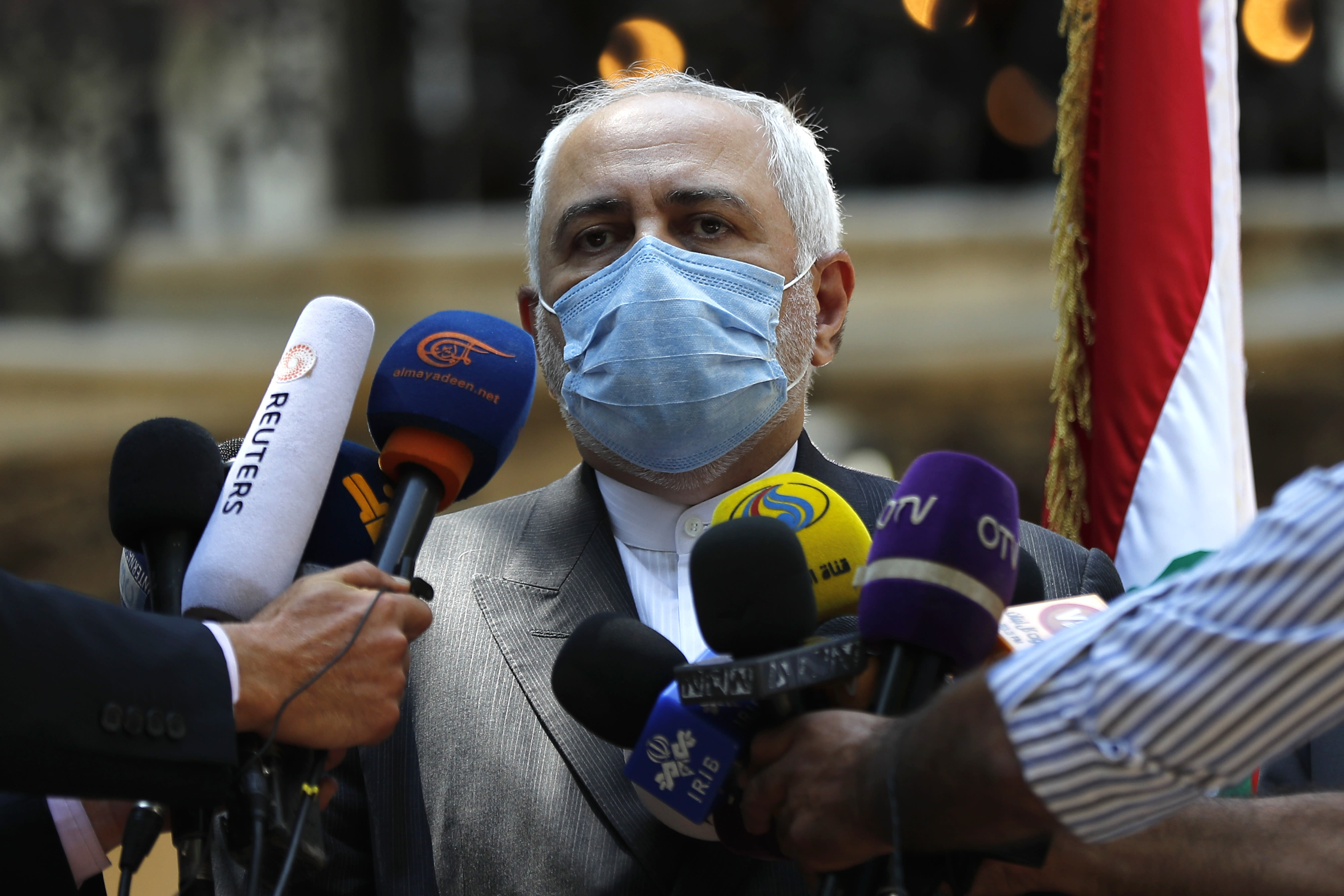 Iranian Foreign Minister Mohammad Javad Zarif speaks outside the Lebanese Foreign Ministry which damaged by last week's explosion that hit the seaport of Beirut, Lebanon, Friday, Aug. 14, 2020. (AP Photo/Hussein Malla)