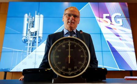 Jochen Homann, President of Germany's Federal Network Agency (Bundesnetzagentur) poses behind a stopwatch for the symbolic start prior to the auction of spectrum for 5G services at the Bundesnetzagentur head quarters in Mainz, Germany, March 19, 2019. REUTERS/Kai Pfaffenbach