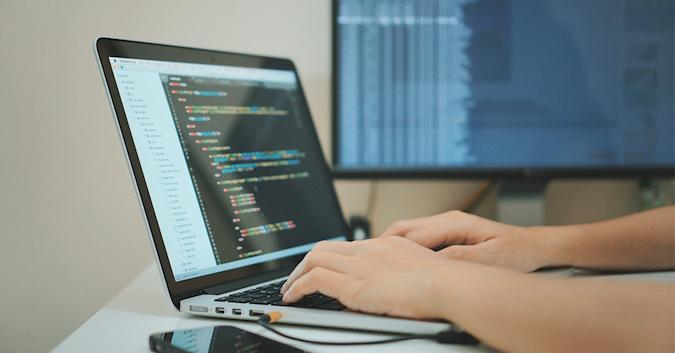 Stock image of someone doing coding work on a laptop.
