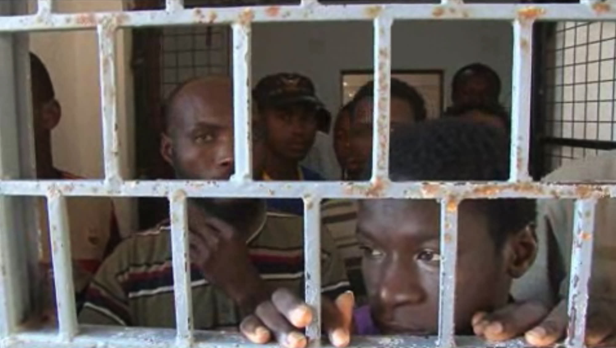 In this image made from Monday, Oct. 14, 2013 video, African migrants look through bars of a locked door at Sabratha migrant detention center for men in Sabratha, Libya. Libya's chaos in the two years following the overthrow of dictator Moammar Gadhafi has turned the country into a prime springboard for tens of thousands of migrants, mainly from Africa, trying to reach Europe in dangerous sea voyages. (AP Photo/AP Video)