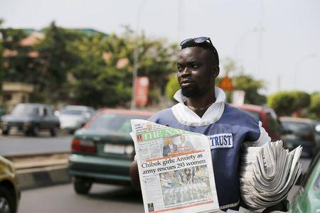 A man sells newspapers, featuring a front page article about Nigerian soldiers rescuing a group of women, in Abuja