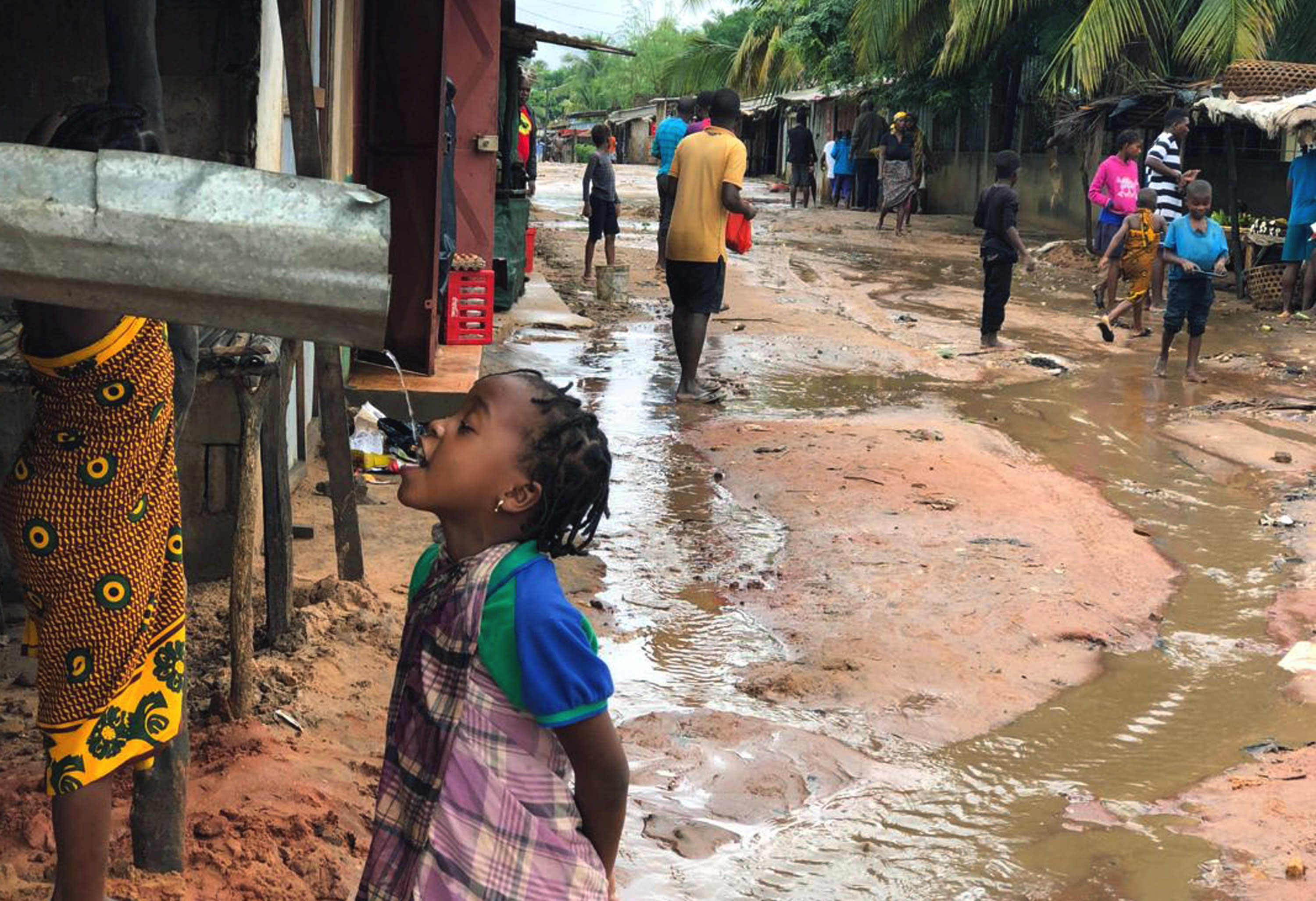 A child drinks water from a gutter during floods due to heavy rains in Pemba, Mozambique, Sunday, April 28, 2019. Serious flooding began on Sunday in parts of northern Mozambique that were hit by Cyclone Kenneth three days ago, with waters waist-high in areas, after the government urged many people to immediately seek higher ground. Hundreds of thousands of people were at risk. (AP Photo/Tsvangirayi Mukwazhi)