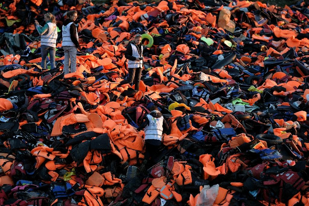 Volunteers stand on a pile of lifejackets left behind by refugees and migrants who arrived on the Greek island of Lesbos after crossing the Aegean Sea from Turkey, on December 3, 2015