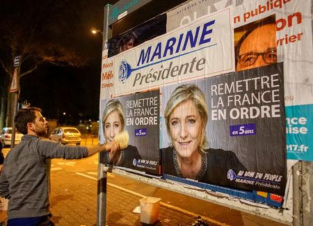 FILE PHOTO: Members of the National Front youths put up posters of Marine Le Pen, French National Front (FN) political party leader and candidate for the French 2017 presidential election, ahead of a 2-day FN political rally to launch the presidential campaign in Lyon, France, February 2, 2017. REUTERS/Robert Pratta/File Photo