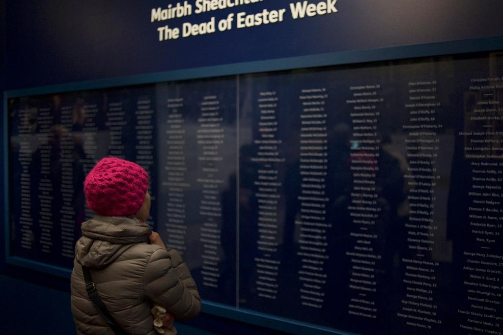 """A visitor browses the list of names of military and civilians (both Irish and British) killed during the Easter Rising of 1916, at the """"Proclaiming a Republic: the 1916 Rising"""" exhibition at the National Museum of Ireland in Dublin (AFP Photo/Paulo Nunes dos Santos)"""