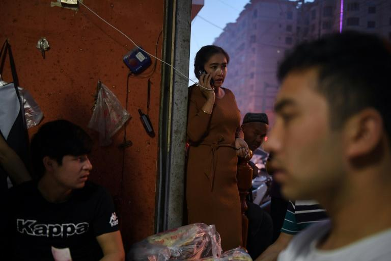 A woman uses a mobile phone outside a restaurant in Hotan in China's northwestern Xinjiang region in 2019 (AFP Photo/GREG BAKER)